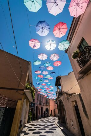 Colorful umbrellas hanging above a street on the occasion of a village festival in southern Italy.