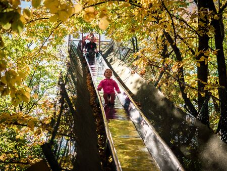 Verona, Italy - October 15, 2017: Little girl has fun on a very long steel slide that passes through the branches of the trees.