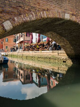 Venice, Italy - April 23, 2017: Characteristic brick pedestrian bridge that crosses one of the many navigable canals in Venice.