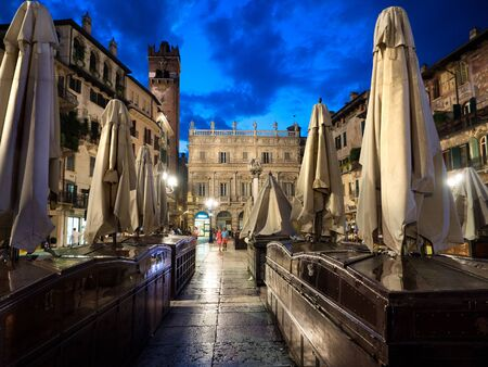 Verona, Italy - July 7, 2018: Tourists and citizens stroll in the evening in the illuminated herb square of romantic Verona, Italy. 版權商用圖片