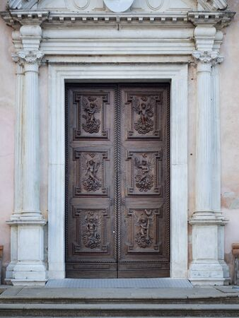 Carved wooden portal with scenes of saints from an ancient Italian church.