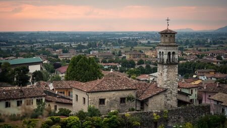 View of the town of Lonato at sunset. In the foreground an ancient bell tower.