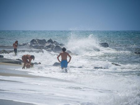 Bathers on the beach during a heavy storm. Waves that crash powerfully on the shore.
