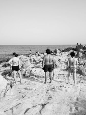 Sardinia, Italy - August 7, 2019: Tourists and bathers on the sand and rock beaches typical of Sardinia.