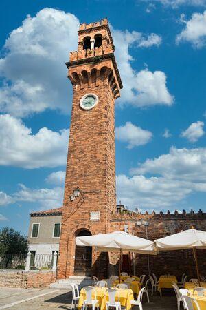 Brick bell tower of the church of San Giacomo in Murano, Venice lagoon island, Italy.