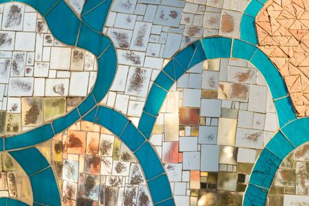 Background formed by glass mosaic tiles with blue lines.