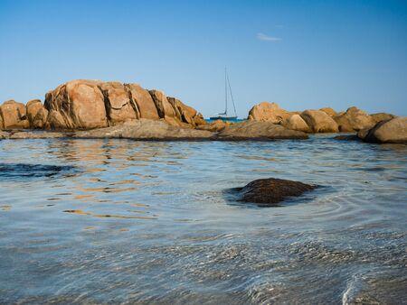 Sailboat sails near the coast and rocks of the transparent sea of Sardinia, Italy.