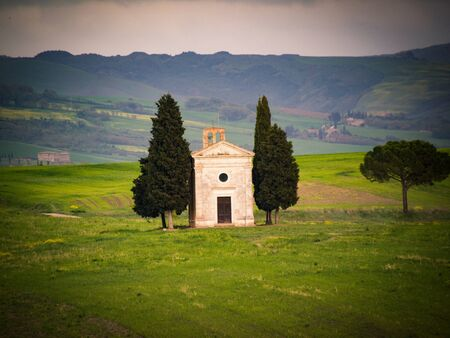 Tuscany at sunset with chapel of Madonna di Vitaleta, San Quirico d'Orcia, Italy.