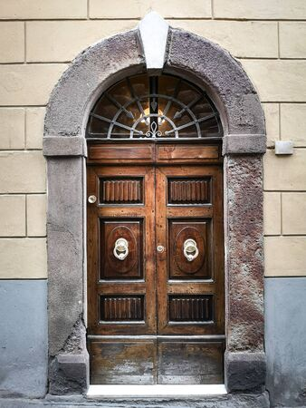 Ancient and solid wooden door with imposing stone arch.