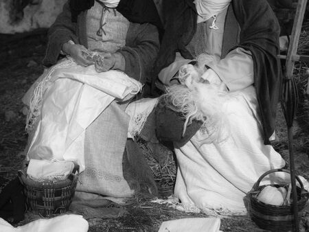 Women from a village work the wool and mend fabrics sitting on a straw bale.