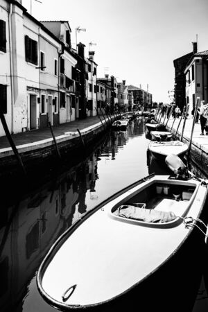 Boat moored in a narrow Venice canal surrounded by houses. 版權商用圖片