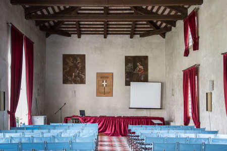 Vicenza, Italy - May 13, 2015: Conference hall with canvas blue chairs and red curtains, inside villa Cordellina Lombardi.