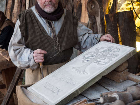 Vicenza, Italy - December 29, 2019: Stonemason carves and shapes the stone with a wooden hammer and chisel.