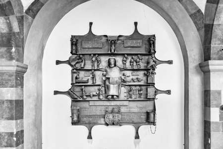 Innichen, Italy - December 25, 2016: Singular funeral plate made of wrought iron with figures in relief. Innichen Cemetery, Italy,