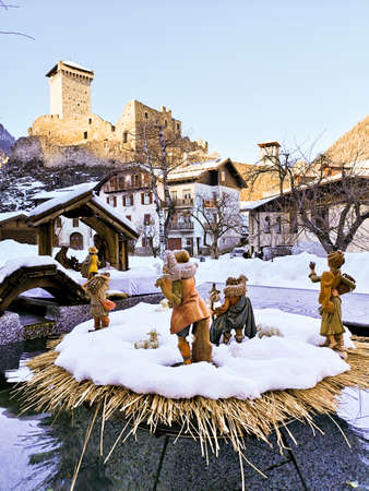 Ossana, Italy - December 26, 2019: Outdoor nativity scene covered in snow. In the background the famous castle of San Michele.