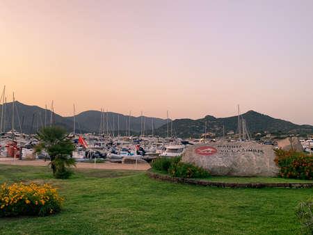 Villasimius, Italy - August 12, 2019: Sunset on the marina of Villasimius. Recreational boats are still in calm water.