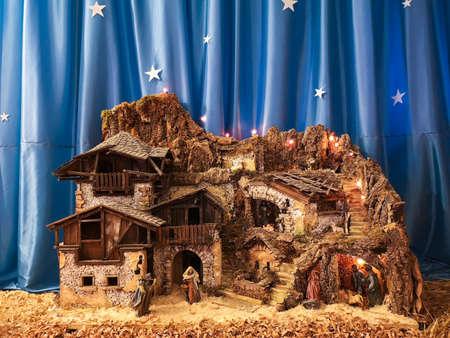 Ossana, Italy - December 26, 2019: Handmade crib nativity scene. In the background starry silk sky.