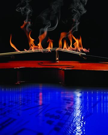 Viool met Strings on Fire over blauw water met bladmuziek Stockfoto