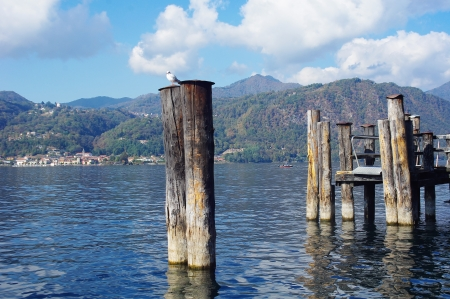 Stakes for tying boats and wooden pier of  town Orta San Giulio on Orta lake, Italy Stock Photo - 17016970