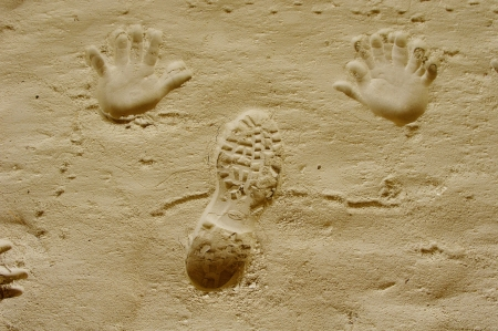 Handprints and trekking shoe print in a sand cave around Nevsha Station, Bulgaria photo