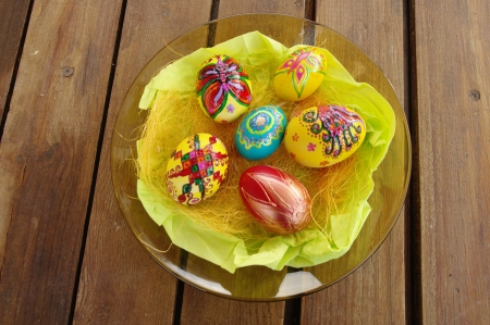 relievo: Hand Painted Easter Eggs in glass plate on wood table Stock Photo