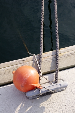 cleat: Tying a yacht on metal cleat on harbor Stock Photo