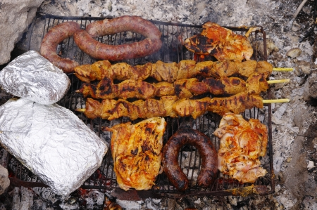 Sausages, steak and pork spit cooking on a grill Stock Photo - 19015871