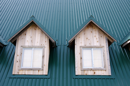 Two dormer with windows on the dark green roof photo