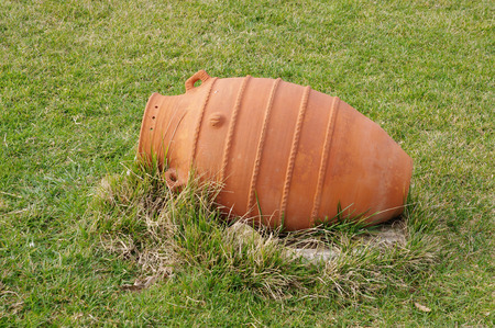 New terracotta vase with antique design laying on the grass, Bulgaria photo