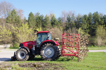 agronomic: Red tractor for plowing on grass on sunny day Stock Photo