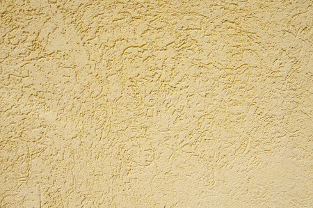 Yellow rough plaster on wall in sunny day photo