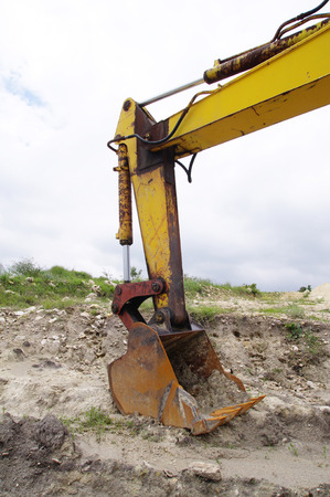 Backhoe excavator in sand quarry in cloudy day photo