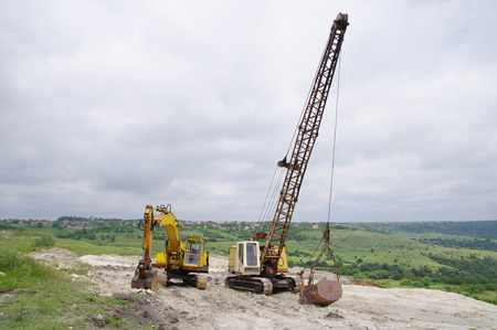 sand quarry: Two different excavator in sand quarry in cloudy day