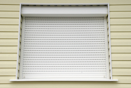 Window with white external blinds from american style house Imagens