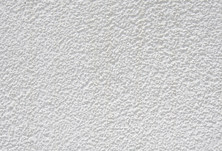 White rough plaster on wall closeup in sunny day photo
