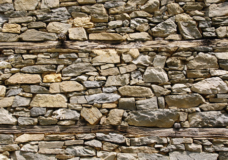 Old stone wall with wooden beams Stock Photo