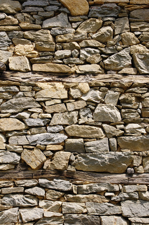 Old stone wall with wooden beams closeup