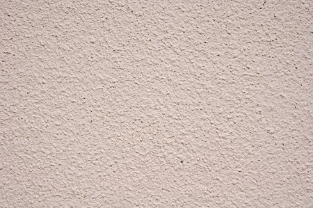 Light pink rough plaster on wall closeup in sunny day photo