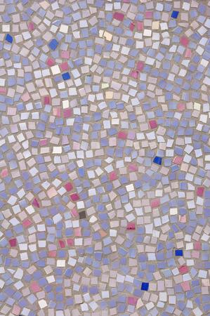 Mosaic of broken tile pieces on wall closeup photo