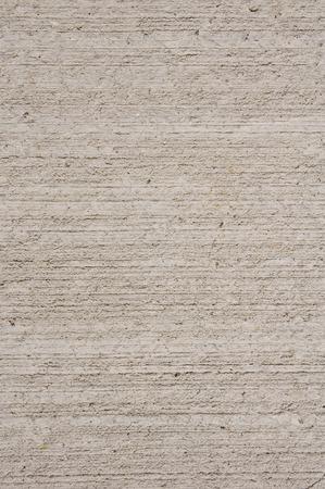 ecru: Ecru rough plaster on wall closeup in sunny day Stock Photo