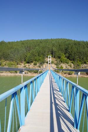 Rope pedestrian bridge on Kardzhali dam, Bulgaria in sunny day photo