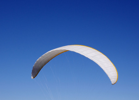 high flier: White paraglider  in the sky  in sunny day