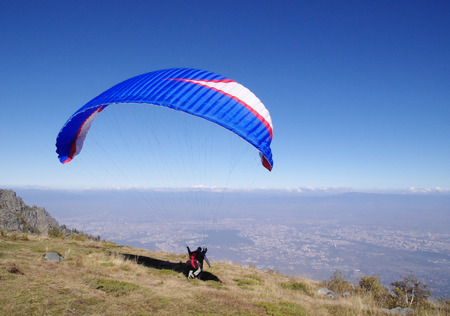high flier: Blue paraglider in the sky over city Sofia, Bulgaria