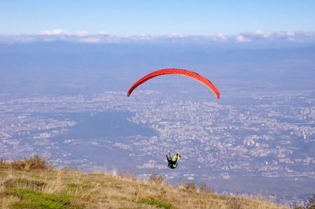 high flier: Red paraglider in the sky over city Sofia, Bulgaria