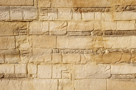 Decorative relief brown and ecru plaster imitating stone wall