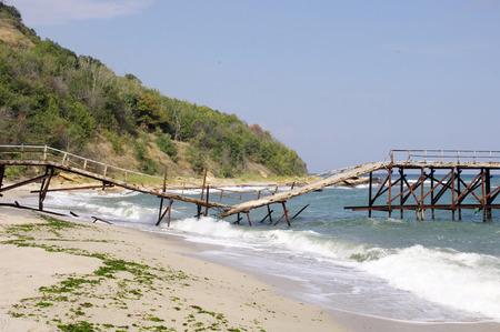 Gebroken brug op strand in zonnige dag Stockfoto