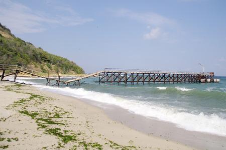 Kapotte brug op het strand in zonnige dag