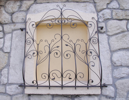 walled: Decorative wrought iron grille on walled window  closeup Stock Photo
