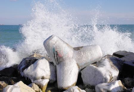 wintriness: Frozen tetrapod  and waves in sunny winter day