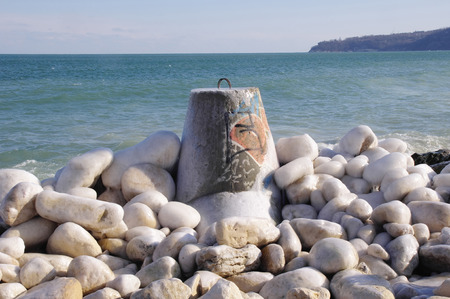 wintriness: Frozen tetrapod  and stones in sunny winter day Stock Photo